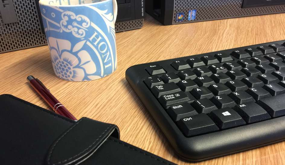 Image of a keyboard, desk pad and mug