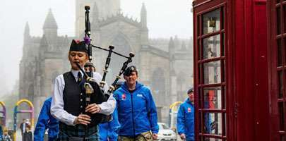 A Legion Scotland piper leads the procession up the Royal Mile.