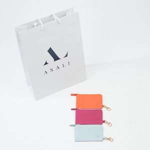 Three different coloured cardholders pictured with a branded ASALI paper gift bag