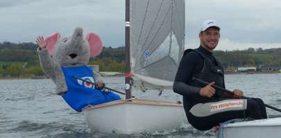 Service personnel sailing with the mascot too hanging over the edge of the boat