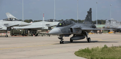 A Grippen Aircraft from the Hungarian Air Force taxiing past the RAF Typhoons.