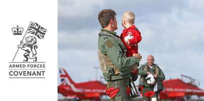 Image showing the Armed Forces Covenant Logo on the left with an image attached of a Red Arrow holding his baby on a homecoming, whilst stood in front of a red arrow aircraft.