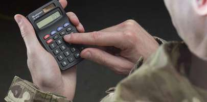 Picture of a serviceman in his camo clothes handling a calculator.