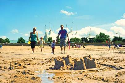 Image of a family walking across a beach in front of some ready-made sandcastles.