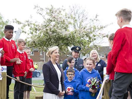 Image HRH meets some of the children, Hannah Avery is holding the posy.