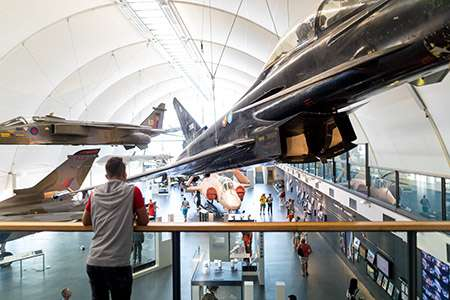 Image of man on gallery overlooking RAF Museum display