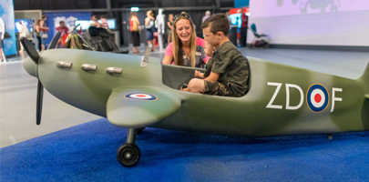 Lady with boy in model spitfire at RAF Museum