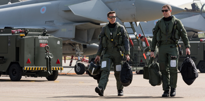 Image shows Two aircrew walking in front of stationary RAF Typhoons