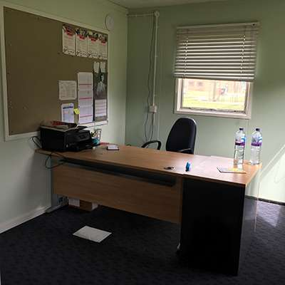 Image shows desk inside Portakabin