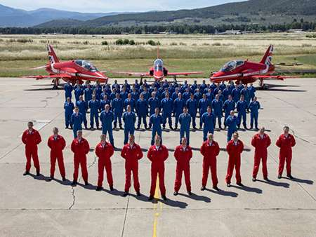Image shows the Red Arrows Team in front of three Red Arrow Hawks.