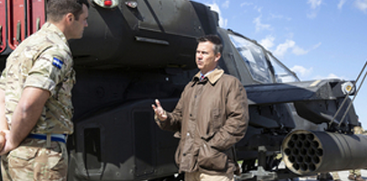 Minister for the Armed Forces Mark Lancaster speaks to a British Army soldier in front of an Apache helicopter, recently deployed to Estonia.