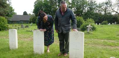 Image of some volunteers looking at one of the Commonwealth War Graves