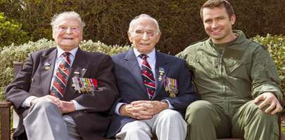 Image of two veterans sat on a garden bench with a current serviceman