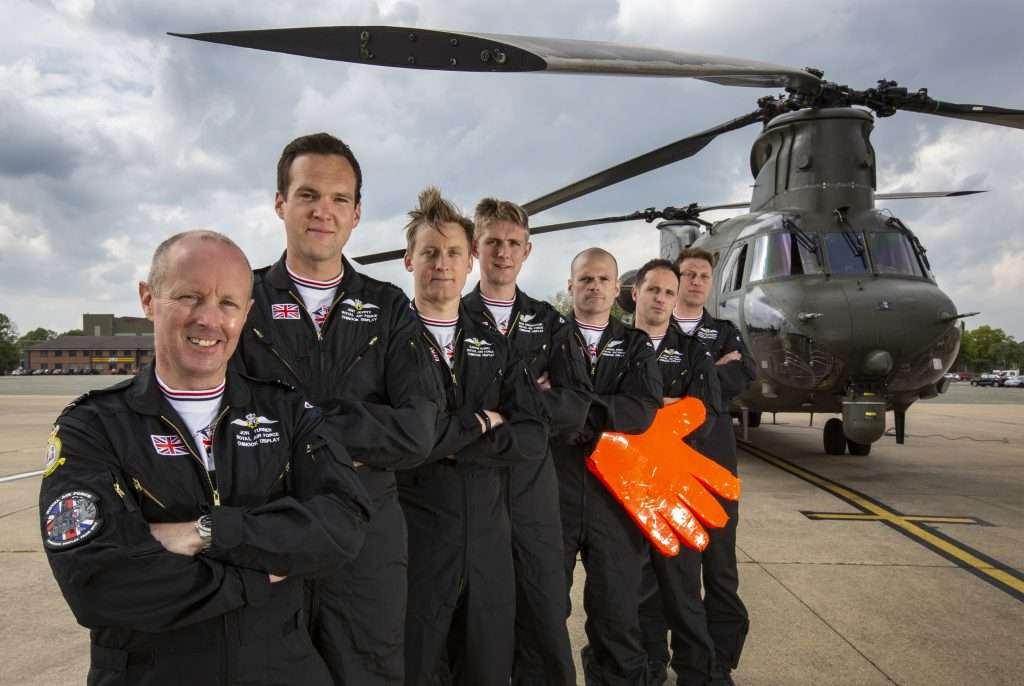 The RAF Chinook Display Team stood infront of a Chinook with the loadmaster holding a big orange foam hand.