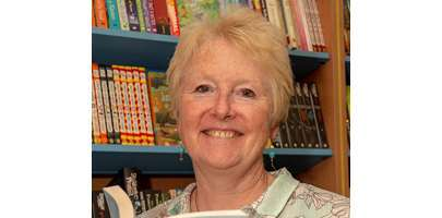 Image of Alison Baverstock holding a book whilst stood in front of some bookshelves.