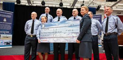 BMT 31 presenting their charity cheque with Senior Student LAC Rutter on the left and OC 4624 Sqn on the right