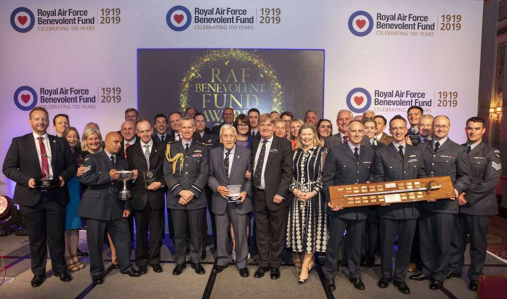 Image shows all the award winners up on stage holding the traditional awards plaque.