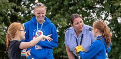 RAF personnel and Airplay worker talking to two of the children who have been helping clean the Commonwealth War Graves.