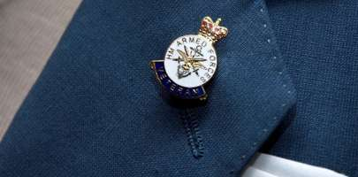 Image of a Veteran's badge on a gentleman's lapel of his suit jacket.