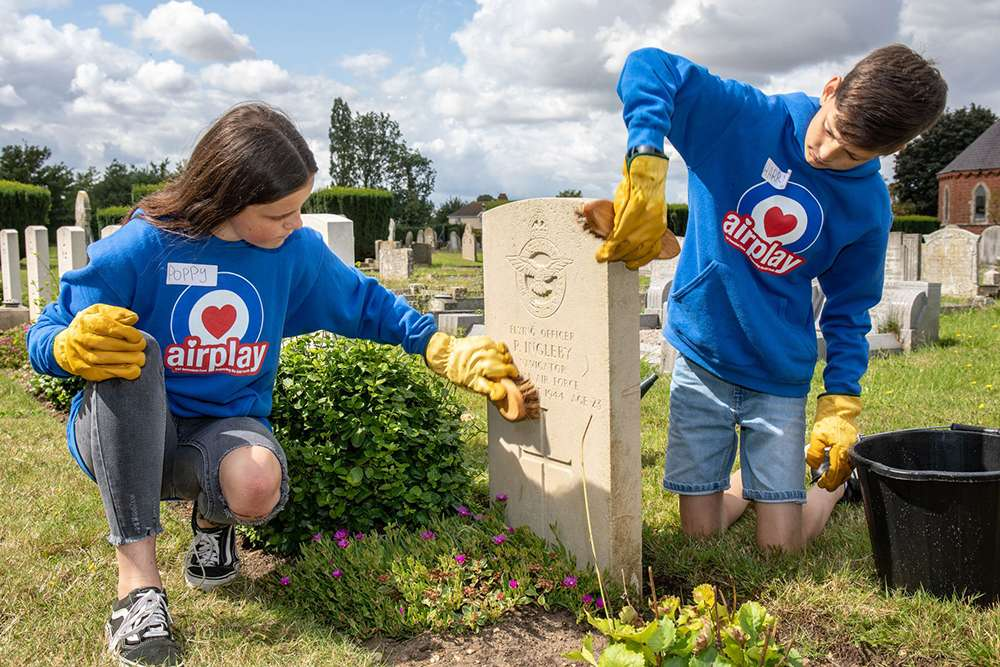 Image shows two children in Benevolent Fund hoodies, cleaning one of the Commonwealth War Graves and looking quite happy!