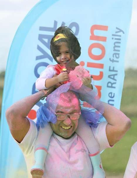 Image of a father and his daughter sat on his shoulders covered in different coloured powder. Taken from the 2018 event.