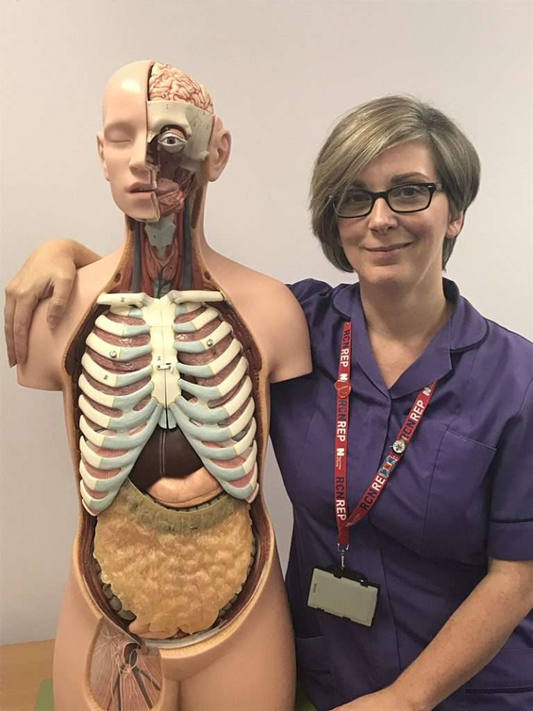 Jane O'Brien holding a skeleton 'model' to link with her job in the NHS.