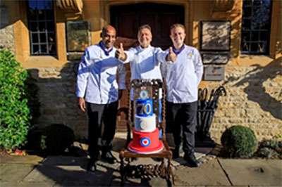 RAF chefs Cpl Vishwaananda Kisten, left, and SAC Ross Haynes, right, with Raymond Blanc and his birthday cake.