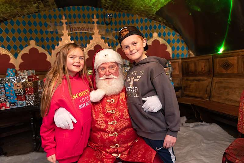 A lovely picture showing Santa crouched down with a little girl and a little boy stood next to him.