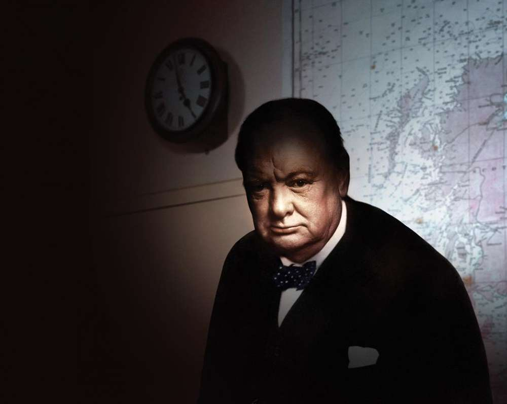 Image showing a shadow'd Winston Churchill stood in the Cabinet War Rooms in front of a Map of the UK on the wall and an old clock.