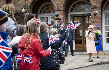 Image shows children from the local Cherry Tree Academy waving flags and cheering Her Majesty The Queen as she prepares to leave RAF Marham after her visit.