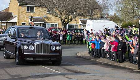 Image shows the arrival of Her Majesty the Queen to Royal Air Force Marham; the route was lined by children from the local Rainbow Daycare Centre, waving Union flags and cheering The Queen on.