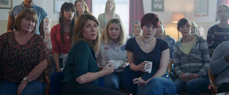 film clip screenshot of all the choir ladies sitting in their meeting where they talk about the start of the choir.