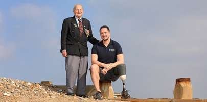 Image of a veteran stood up on a bank with a younger veteran kneeling on the ground.