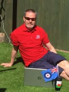 Image of Evidence Manager, Richie Morgan sat in his garden with his laptop, Welsh thermal drinking cup and an RAF Flag sticking out of it.