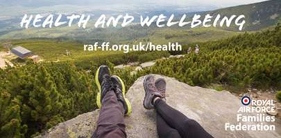 Health and Wellbeing themed image of two people sitting on the top of a mountain with their feet crossed, looking out across an amazing view