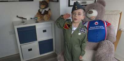 Jacob the Pilot at home saluting in his green RAF Flying Suit