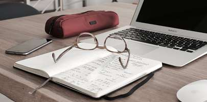 Free use image representing someone's desk space with an open notepad and glasses laid across.