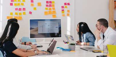 Image of colleagues working around a table with post-it notes up on a white wall and TV screen.